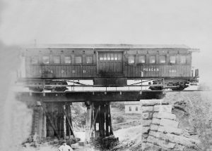 Rail car stopped on the overpass.  Unknown date, but looking at the structure, it was before the train station was built.
